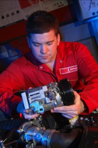 A technician checks over a Denso compressor